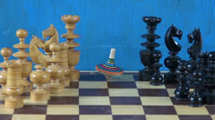 Colorful wooden whirligig  on chessboard with chessmen Stock Footage