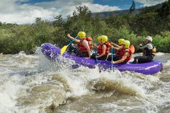 A Group Of Men And Women With A Guide White Water Rafting On The Patate River - stock photo