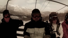 Skiers riding on cold ski lift in storm Stock Footage