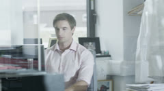 Casually dressed young professional man on the phone in a modern office - stock footage