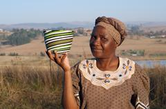 traditional african zulu woman selling wire baskets - stock photo