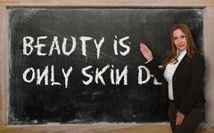 teacher showing beauty is only skin deep on blackboard - stock photo
