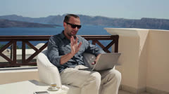 Handsome man chatting on laptop on beautiful terrace HD Stock Footage