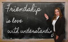 Stock Photo of teacher showing friendship is love with understanding on blackboard
