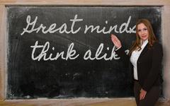 teacher showing great minds think alike on blackboard - stock photo