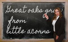 Teacher showing great oaks grow from little acorns on blackboard Stock Photos