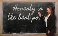 Stock Photo of teacher showing honesty is the best policy on blackboard