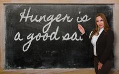 Teacher showing hunger is a good sauce on blackboard Stock Photos