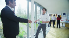 Businessmen meet and shake hands in bright open plan office space - stock footage