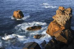 ocean swirling around a rocky outcrop - stock photo