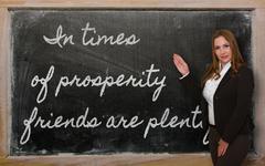 Stock Photo of teacher showing in times of prosperity friends are plentiful on blackboard