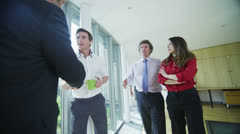 Business group meet and shake hands in bright open plan office space - stock footage