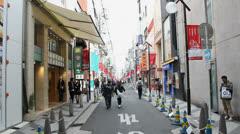 Pedestrians walk in an alley off of Shinsaibashi Suji shopping street in Osaka. Stock Footage