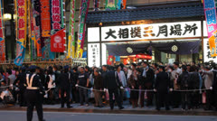 People crossing a busy street after the Grand Sumo Tournament. - stock footage