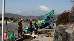 Japanese workers in Hakone work on a road with Mount Fuji in the background. Stock Footage