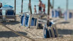 Tourists beach deckchairs Stock Footage