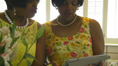 Two women looking at something on a tablet pc Stock Footage
