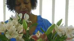 woman with flower arrangement smiles at camera - stock footage