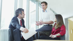 Casual and informal business meeting, colleagues sit together and share ideas - stock footage