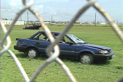 Disaster, Damaged car thru fence, 1992 Hurricane Andrew damage Stock Footage