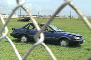 Stock Video Footage of Damaged car thru fence, 1992 Hurricane Andrew damage