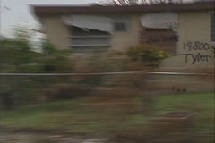 Disaster, Drive by quick zoom out badly damaged houses, police car turns corner Stock Footage