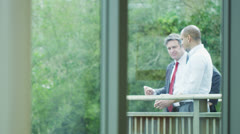 Businessmen chatting together on an outdoor terrace surrounded by trees Stock Footage
