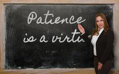 teacher showing patience is a virtue on blackboard - stock photo
