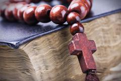 Wooden rosary and the bible Stock Photos