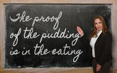 teacher showing the proof of the pudding is in the eating on blackboard - stock photo