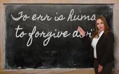 teacher showing to err is human, to forgive divine on blackboard - stock photo