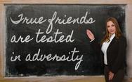 Stock Photo of teacher showing true friends are tested in adversity on blackboard