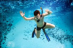 Teenager in the mask and snorkel swim underwater. Stock Photos