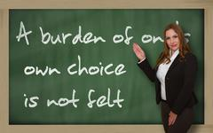 teacher showing a burden of one's own choice is not felt on blackboard - stock photo