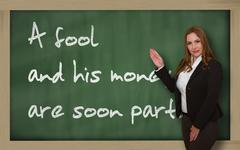 teacher showing a fool and his money are soon (easily) parted on blackboard - stock photo