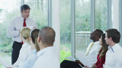 Diverse group of business people listening to a business presentation - stock footage