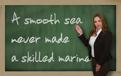 teacher showing a smooth sea never made a skilled mariner on blackboard - stock photo