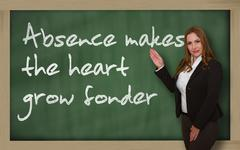 Teacher showing absence makes the heart grow fonder on blackboard Stock Photos