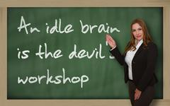 Teacher showing an idle brain is the devil's workshop on blackboard Stock Photos