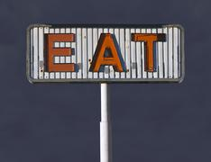 old eat sign with storm sky - stock photo