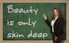 Teacher showing beauty is only skin deep on blackboard Stock Photos