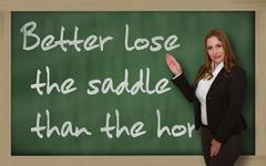 teacher showing better lose the saddle than the horse on blackboard - stock photo