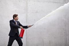 focused businessman using a fire extinguisher - stock photo