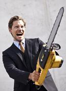 angry businessman with blurred chainsaw - stock photo