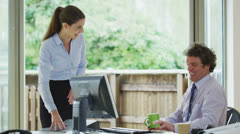 Cheerful businessman and his secretary in a light and natural office environment Stock Footage