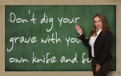 Teacher showing don't dig your grave with your own knife and fork on blackboa Stock Photos