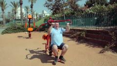 Mature man exercising on Lat Pull fitness machine outdoor Stock Footage