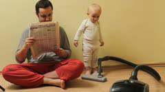 Funny moment, father reads the newspaper and ask his little baby to clean  house Stock Footage