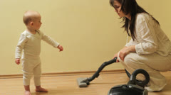 Cute little baby look how his mother clean the house with vacuum cleaner Stock Footage