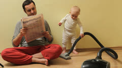 Funny moment, father read the newspaper, children clean with aspirator Stock Footage